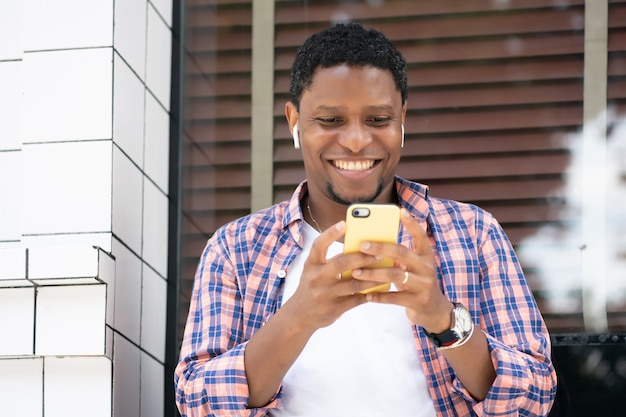 Hombre afroamericano que usa su teléfono móvil mientras está sentado en el escaparate de una tienda en la calle. concepto urbano.