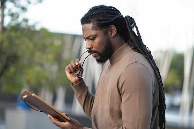 Hombre afroamericano, con rastas y gafas, leyendo un libro al atardecer