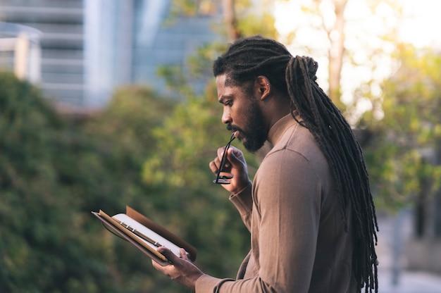 Hombre afroamericano con rastas y ropa de invierno, colores marrones leyendo un libro en el parque