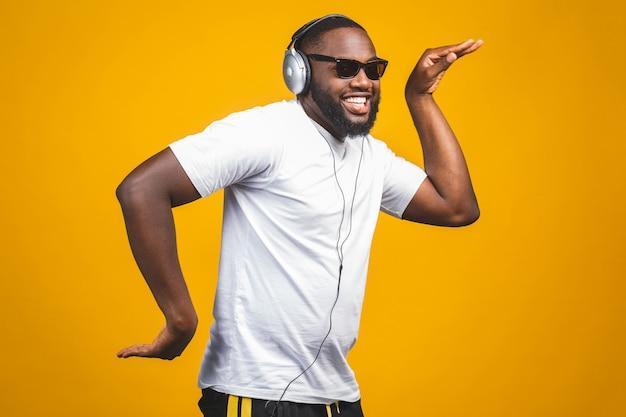 Hombre afroamericano en ropa casual y auriculares escuchando música y bailando.