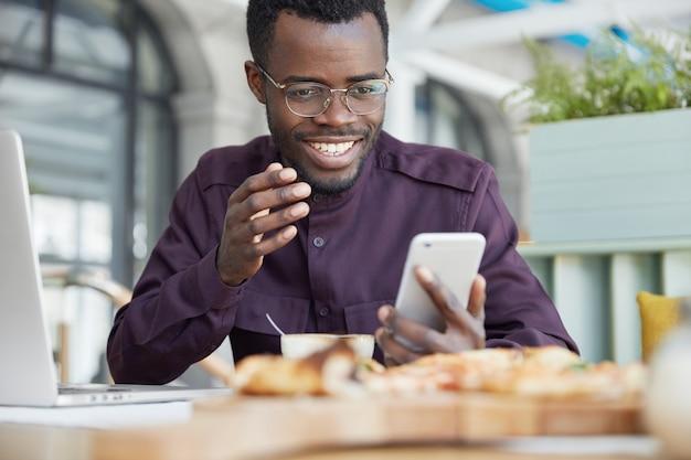 Hombre afroamericano con ropa formal, comparte archivos multimedia en el mensaje, escribe comentarios, organiza el horario
