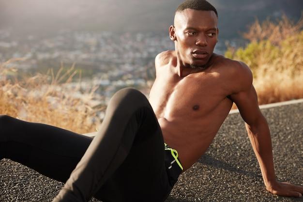 Hombre afroamericano sano se relaja solo en la carretera de montaña, cansado del entrenamiento matutino, plantea un hermoso paisaje al aire libre