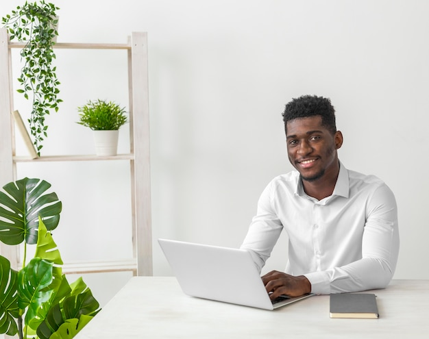 Hombre afroamericano sentado en el escritorio y sonríe