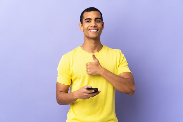 Hombre afroamericano sobre pared púrpura aislado mediante teléfono móvil dando un gesto de pulgares arriba
