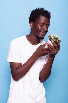 Hombre afroamericano sonriendo y mirando maceta con planta