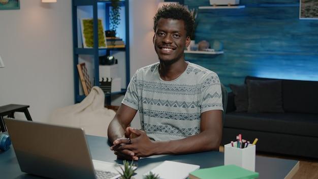 Hombre afroamericano sonriendo y trabajando en equipo portátil