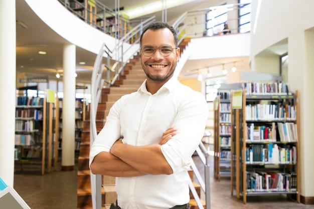Hombre afroamericano sonriente que presenta en la biblioteca pública