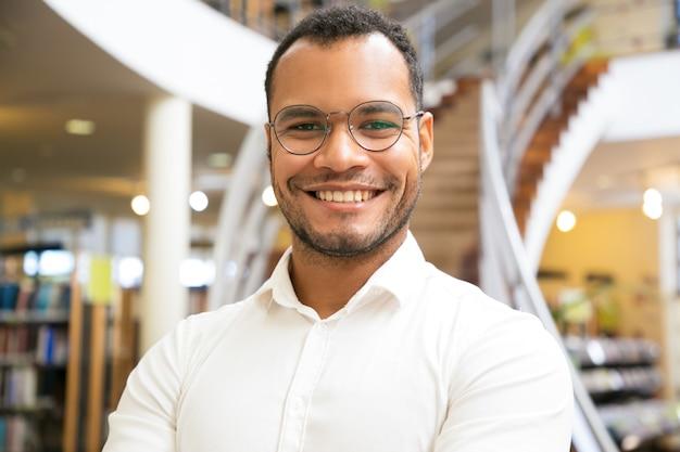 Hombre afroamericano sonriente que presenta en la biblioteca