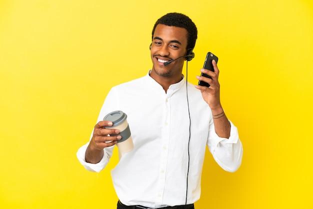 Hombre afroamericano telemarketer trabajando con un auricular sobre fondo amarillo aislado sosteniendo café para llevar y un móvil