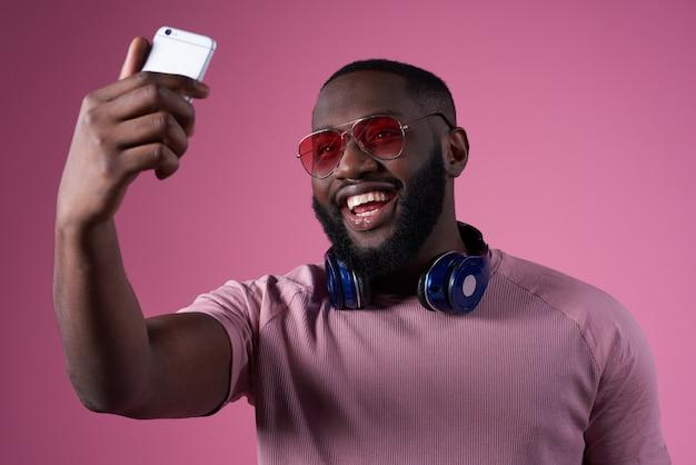 Hombre afroamericano tomando selfie aislado.