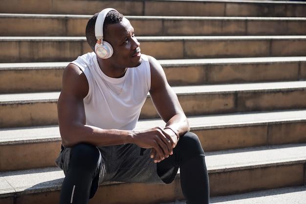 Hombre afroamericano tomar un descanso y escuchar música en línea en el teléfono inteligente después de hacer ejercicio.