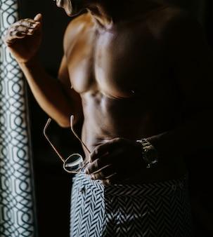 Hombre afroamericano con torso desnudo se prepara parado de pie antes