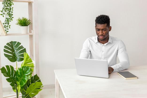 Hombre afroamericano trabajando y planta monstera