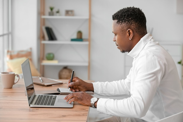 Hombre afroamericano trabajando en un portátil en la oficina