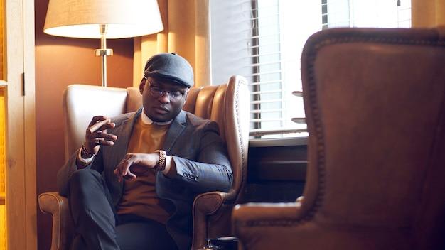 Hombre afroamericano en traje y gafas está sentado en una silla en un restaurante, cafetería, mirando su reloj mientras espera a su amigo