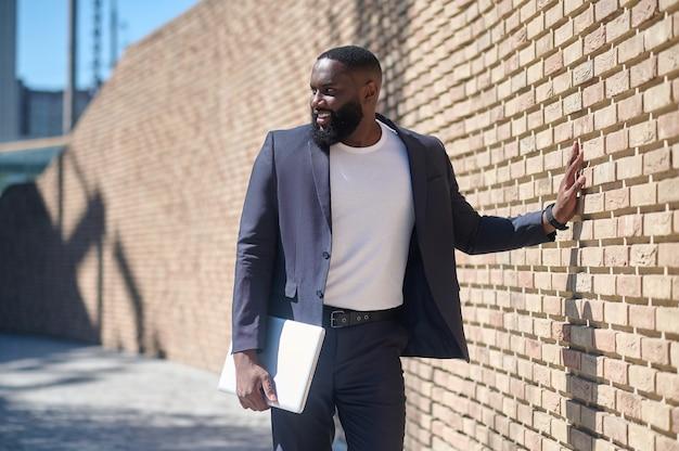 Un hombre afroamericano en un traje de pie cerca de la pared de ladrillos