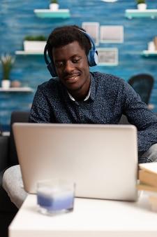 Hombre afroamericano usando audífonos usando laptop
