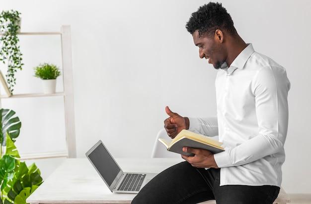 Hombre afroamericano con una videollamada y sosteniendo un libro