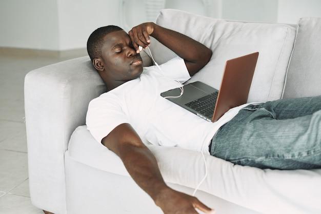 Hombre afroamericano viendo una película en la computadora portátil, descansando en el sofá