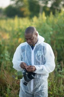 Hombre afroamericano vistiendo protección química y máscara de gas