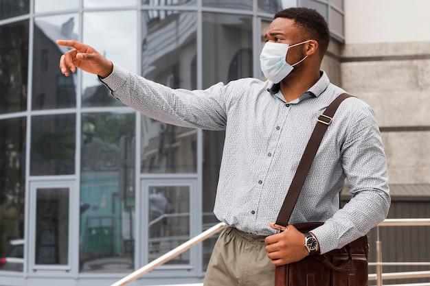 Hombre afuera apuntando a algo mientras se dirigía al trabajo durante la pandemia