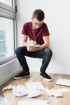 Hombre agachado y apoyado en una pared blanca escribiendo