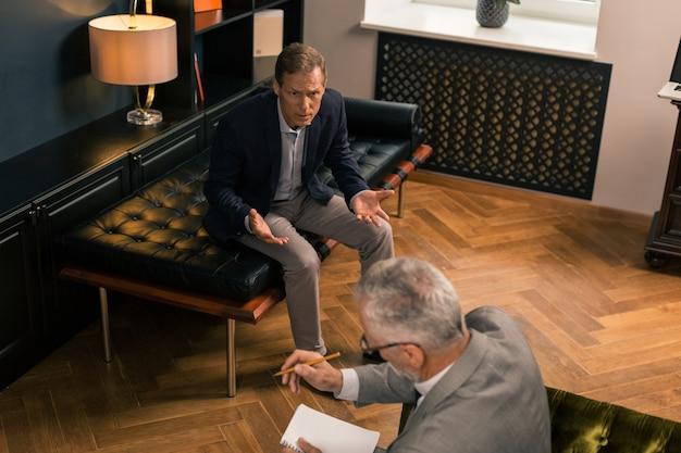 Hombre agitado. vista superior de un hombre incómodo de mediana edad sentado en el sofá mientras habla emocionalmente con su médico