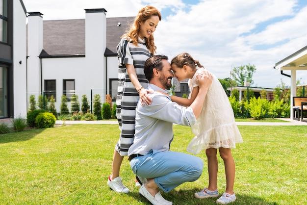 Hombre agradable alegre de pie con su hija mientras le muestra su amor