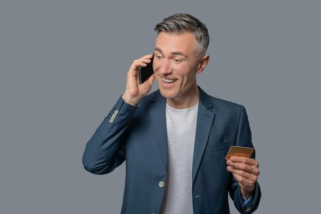 Hombre agradablemente sorprendido hablando por teléfono inteligente