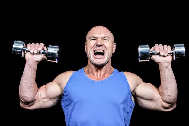 Hombre agresivo levantando pesas