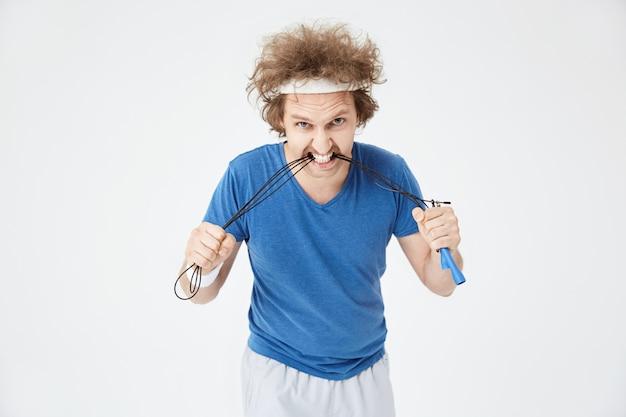 Hombre agresivo en traje deportivo brillante mordiendo saltar la cuerda
