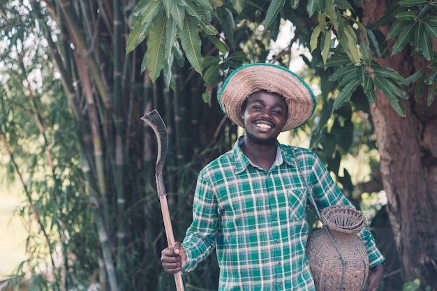 Hombre agricultor africano con cuchillo en campo