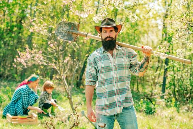 Hombre agricultor ouple con hijo jardinería en el jardín del patio trasero familia trabajando juntos en la granja
