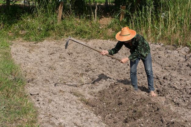 Hombre agricultor sosteniendo la espada en el campo en nakhon phanom, tailandia
