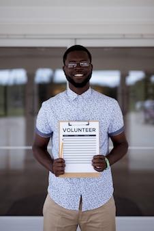 El hombre agujerea un portapapeles voluntario mientras sonríe