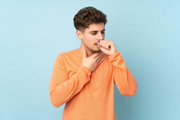 El hombre aislado en la pared azul sufre de tos y se siente mal