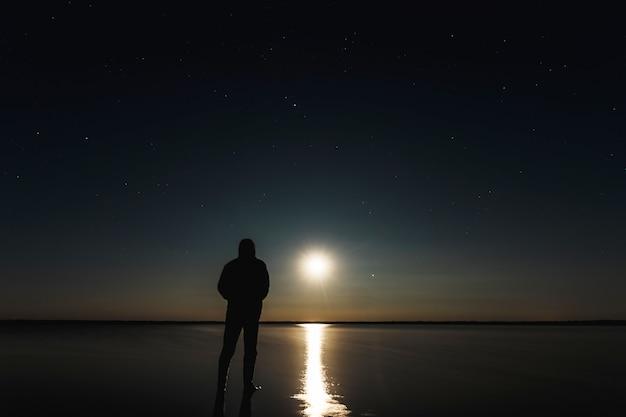 El hombre se para al atardecer de la luna bajo el cielo estrellado.