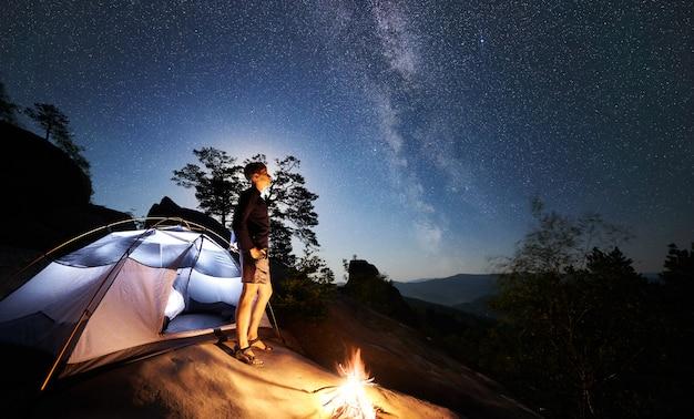 Hombre al lado del campamento, fogata y carpa turística en la noche