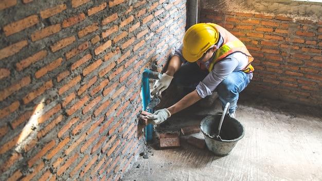 Hombre albañil instalando ladrillos en sitio en construcción