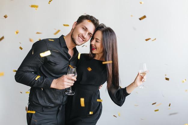 Hombre alegre abrazando a su esposa en la fiesta de cumpleaños de un amigo