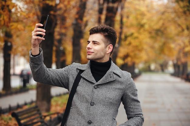 Hombre alegre en abrigo tomando fotos de la naturaleza o haciendo selfie usando un teléfono inteligente negro, mientras camina por el boulevard