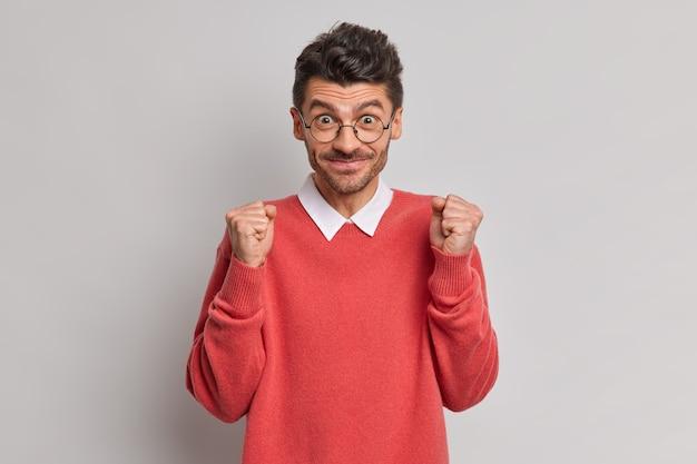 Hombre alegre sin afeitar levanta los puños con anticipación espera algo bueno