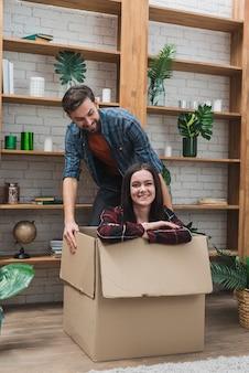 Hombre alegre arrastrando caja con mujer