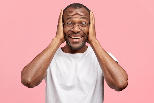 El hombre alegre y asombrado recibe felicitaciones, mantiene ambas manos en la cabeza, tiene una amplia sonrisa amistosa, aislada sobre una pared rosa
