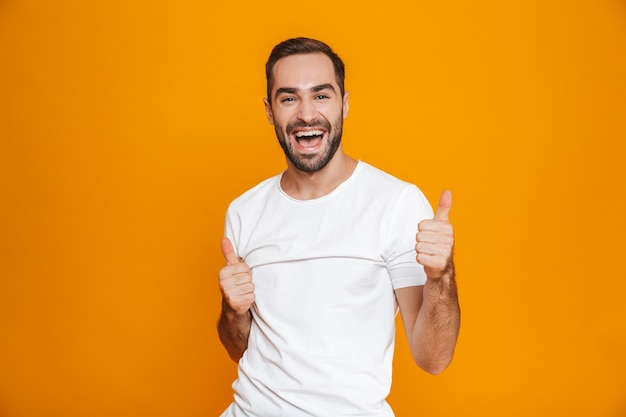 Hombre alegre con barba y bigote mostrando el pulgar hacia arriba mientras está de pie, aislado en amarillo
