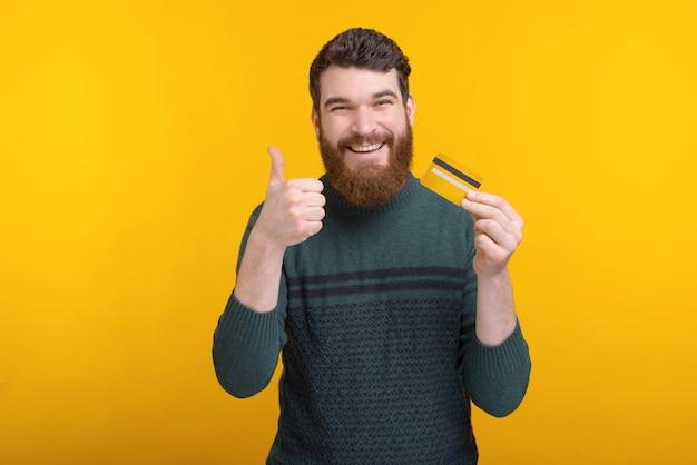 Hombre alegre con barba con tarjeta de crédito y mostrando pulgares arriba gesto