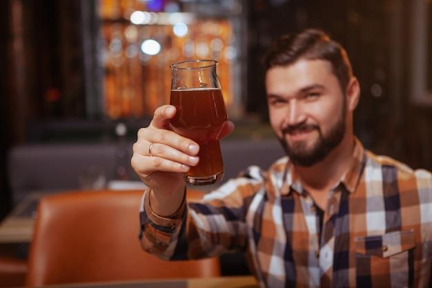 Hombre alegre brindando con su vaso a la cámara