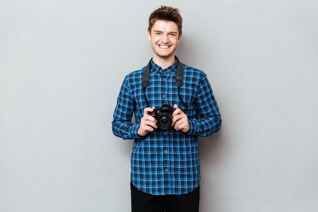 Hombre alegre con cámara posando aislado