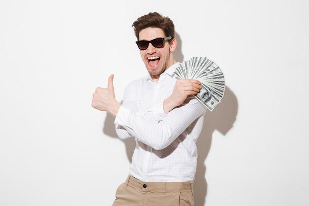 Hombre alegre en camisa y gafas de sol regocijándose mientras demuestra fanático del dinero en dólares y mostrando el pulgar hacia arriba, aislado sobre la pared blanca con sombra