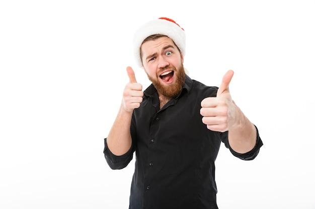 Hombre alegre en camisa y gorro de navidad mostrando los pulgares para arriba